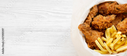 Fast food: fried chicken legs, spicy wings, French fries and tender strips in paper box over white wooden background, top view Fototapet