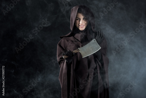 woman in death costume holding cleaver in smoke on black Fototapet