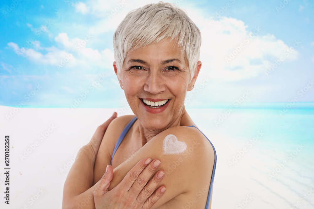 Leinwandbild Motiv - glisic_albina : Woman applying Sunscreen spray / sunblock lotion outdoors outdoor on the beach