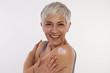 Leinwandbild Motiv Sun protection, Mature Skin care . Woman applying moisturizing cream, hugging herself .