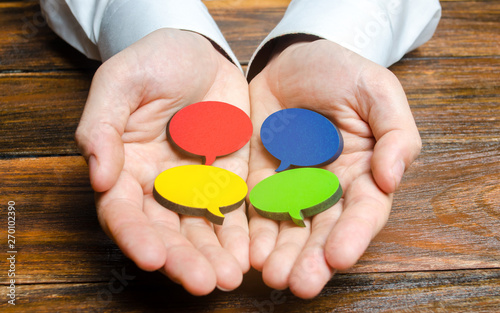 Valokuva  Man holds multicolored speech bubbles in his hands