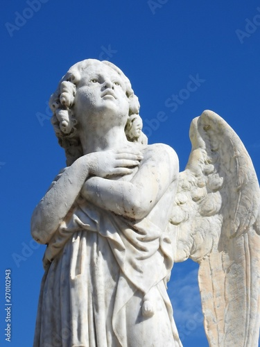 Fényképezés Scene in a graveyard: close-up of an old stone statue of an angel with arms crossed in the chest and looking at the sky