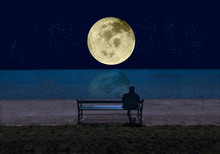 Man Sitting On A Bench By The Sea In The  Night And Looking At A Big Shining Full Moon With Stars Reflecting In The Water. Elements Of This Image Furnished By NASA - Image