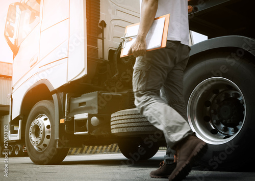 Fotografie, Obraz  truck driver walking around semi truck his inspecting safety of the truck