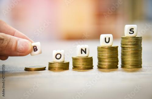 Fototapeta Yearly Bonus concept / hand holding words of bonus on stack coins staircase obraz
