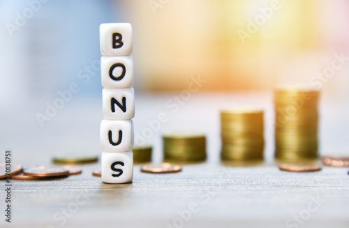 Fototapeta Yearly Bonus concept / words of Bonus and Stack coins on background for Encouragement Morale on the table office obraz