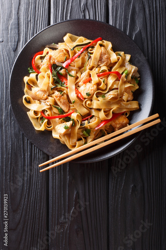 This stir-fry of wide rice noodles with chicken and fresh basil in a spicy, sweet and tangy sauce  close-up on a plate. Vertical top view