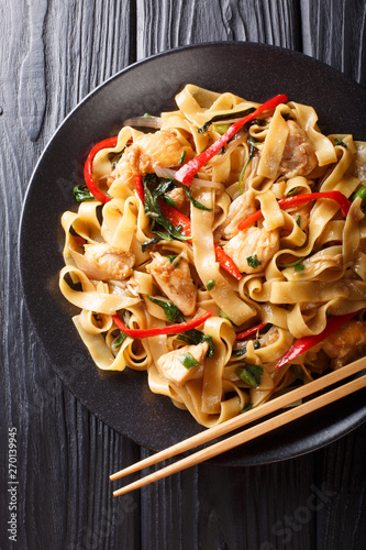 Fotografie, Tablou  Drunken noodles pad kee mao with chicken, basil, chili pepper and sauce close-up on a plate