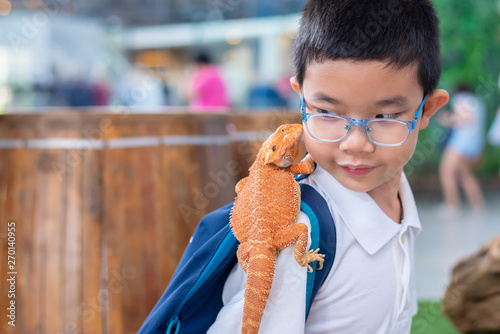 Fotografering boy hold Bearded Dragon on shoulder.