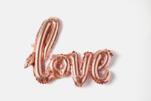 Balloon In The Form Of Inscription Love. Rose Gold Color Decor On A White Background. Flat Lay
