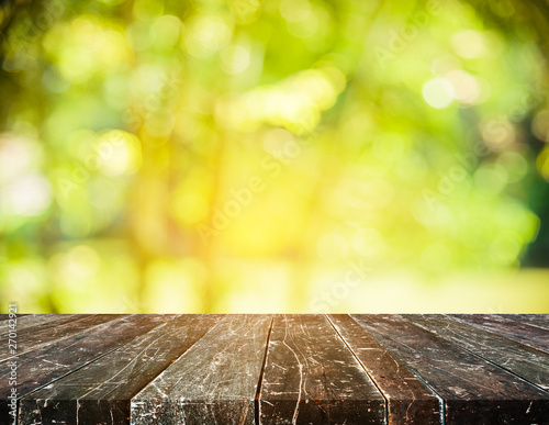 Foto auf Gartenposter Gelb wood table and image of green bokeh.