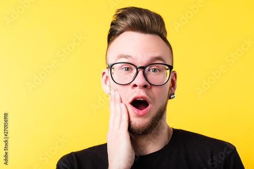 Fotografija  Portrait of impressed millennial guy on yellow background