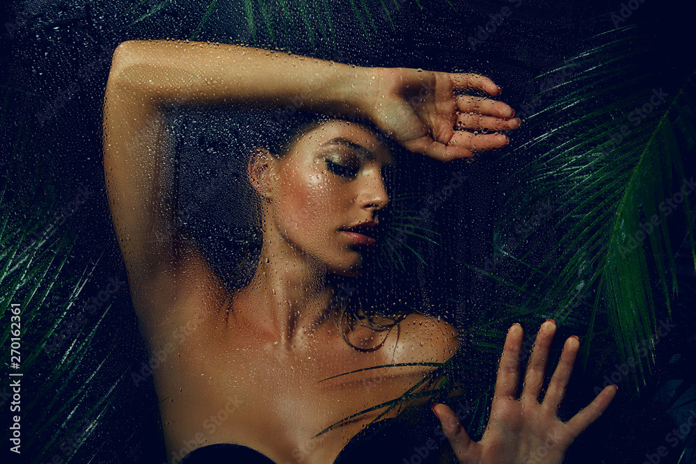 Fototapety, obrazy: A beautiful, young, tanned girl with wet hair and wet skin is standing in the jungle in the rain.
