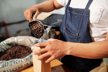 Close-up Of Man Packing Coffee Beans From Shovel Into The Coffee Bag While Working On Coffee Factory