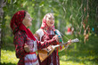 Leinwandbild Motiv Two young woman in traditional russian clothes singing in the forest. One of them playing balalaika
