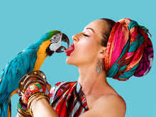 Portrait Of Young Attractive Woman In African Style Holding Ara Parrot On Her Hand And Kissing It By Tongue On Blue Background