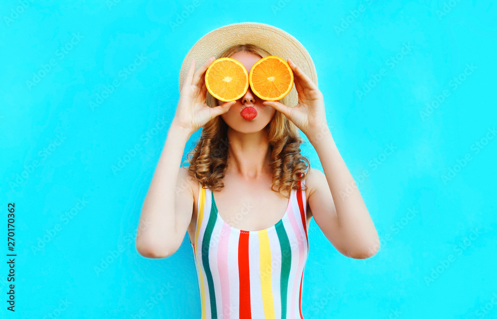 Fototapeta Summer portrait woman holding in her hands two slices of orange fruit hiding her eyes in straw hat on colorful blue background