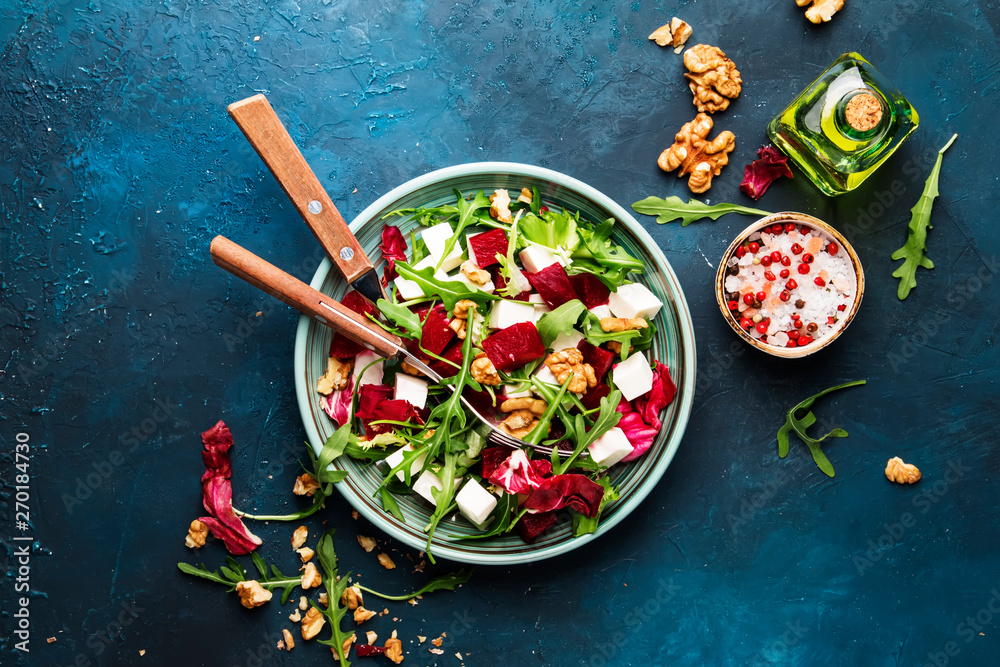 Fototapety, obrazy: Beet summer salad with arugula, radicchio, soft cheese and walnuts on plate with fork, dressing and spices on blue kitchen table, copy space, top view