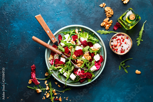 Fototapeta Beet summer salad with arugula, radicchio, soft cheese and walnuts on plate with fork, dressing and spices on blue kitchen table, copy space, top view obraz