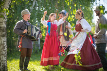People In Traditional Russian Clothes Are Dancing In The Woods - One Of Them Plays The Accordion And Singing