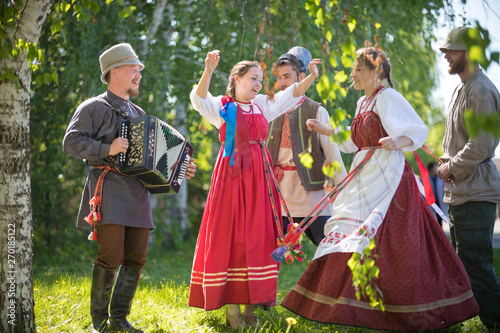 Photo  People in traditional Russian clothes are dancing in the woods - one of them pla