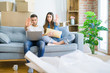Young beautiful couple relaxing sitting on the sofa of new house using computer laptop with open hand doing stop sign with serious and confident expression, defense gesture