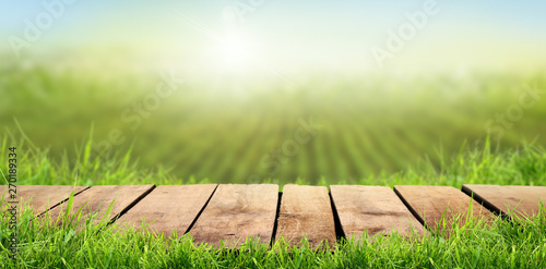Fotografia  A wooden table with a sunny summers farmland background