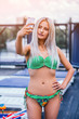 Platinum blonde slim girl in a swimming suit is taking a selfie