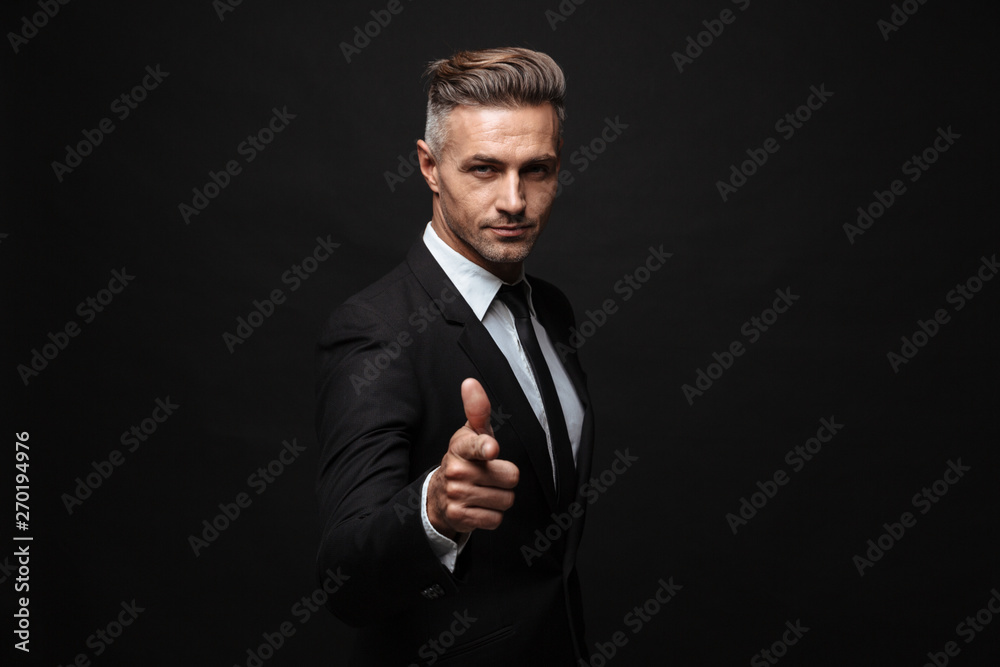 Fototapeta Handsome mature business man posing isolated over black wall background pointing to you.