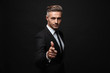 Leinwanddruck Bild - Handsome mature business man posing isolated over black wall background pointing to you.