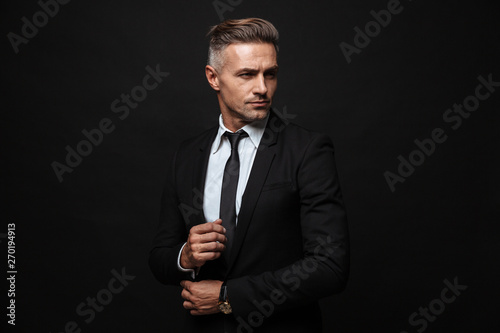 Obraz na płótnie Handsome mature business man posing isolated over black wall background