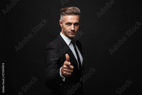 Photo  Handsome mature business man posing isolated over black wall background pointing to you