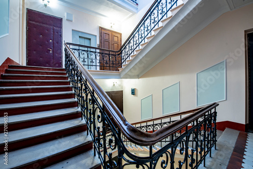 Staircase with forged railings on the railing in the old stairwell