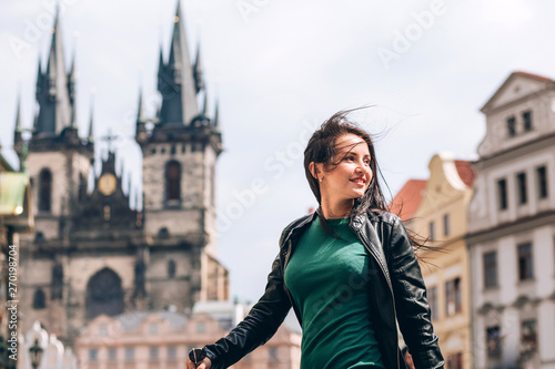 Stampa su Tela  Street portrait of adorable brunette woman with long hair posing at Old Town Square in Prague