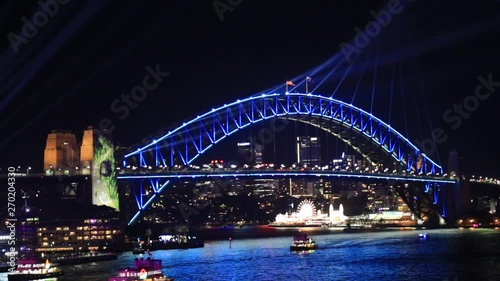 Fotografie, Obraz  Bright colours on the arch of Sydney Harbour bridge over waters of Harbour at night with blue laser beams of Vivid Sydney light show