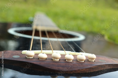 Black guitar lying on the green lawn with a focus on the strings - 270207538