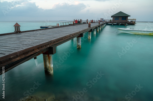 long exposure of wooden dock over cyan water Wallpaper Mural