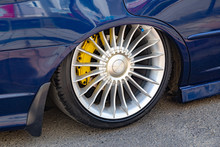Low Rider Car Tuning. Closeup On The Wheel With Lowered Arch And Colored Braking System. Car And Automibile Industry Background.