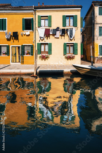 Fotomural  Laundry dries on the facades of colorful houses with reflection in canal, Burano