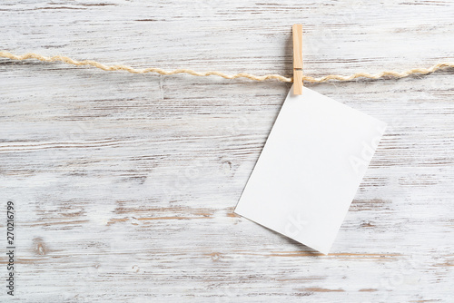 Blank sheet of white paper hanging on twine rope