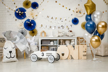 Birthday Decorations With Gifts, Toys, Garlands And Figure For Little Baby Party On A White Bricks Background.