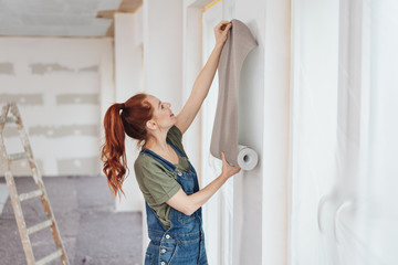 Young woman trying out new wallpaper at home