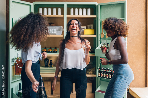 Foto  three multiracial women drinking and dancing in modern apartment