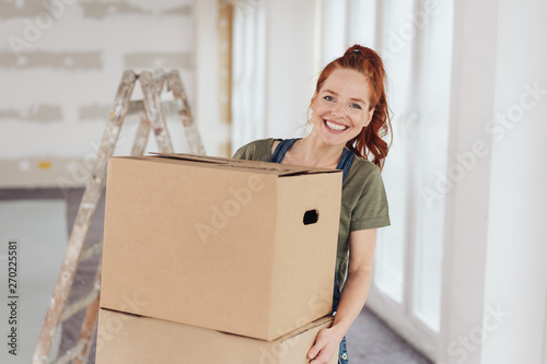 Foto Happy vivacious young woman moving house