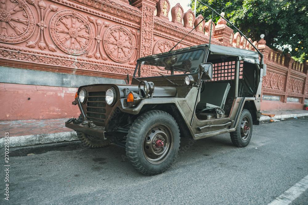 Fototapeta Restored retro jeep Willis during the American Vietnam war on the sand in the desert of Vietnam