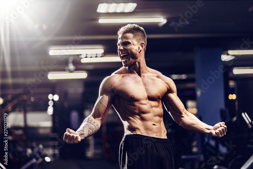 Photo Side view of a caucasian handsome fitness model posing in the gym