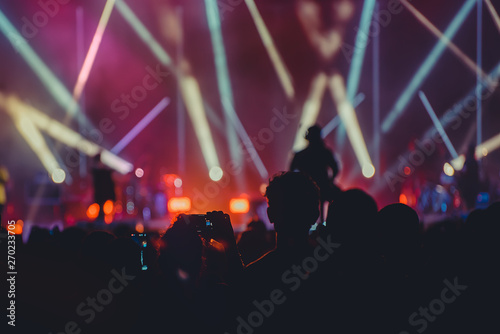 Silhouette image and Defocus of entertainment concert colorful lighting on stage,Audience taking photos of artist,blurred Live Concert and disco party. - 270233705