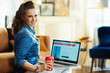 woman with red coffee cup and online travel site on laptop