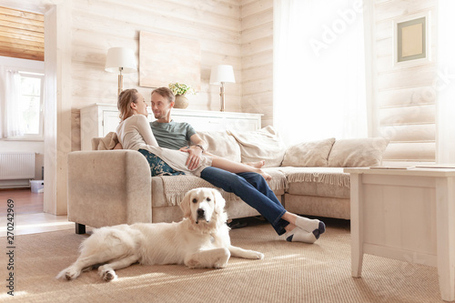 Happy married couple in casual clothes romantically spend a weekend with each other sitting close to her beloved dog in the living room of a country house - 270242969