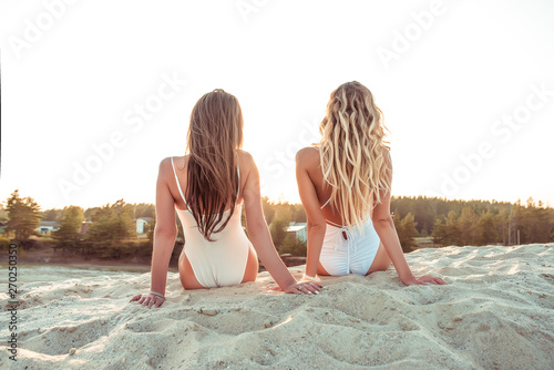 Obraz Two girlfriends woman long hair, view from back, girls sisters, sit sunbathe summer beach white sand near sea lake. Concept style new trend, weekend rest fresh air. Active lifestyle burning outdoors. - fototapety do salonu
